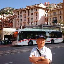 モナコ駅入口前に止まったハイブリッドバスが、二酸化炭素削減を大きく広告