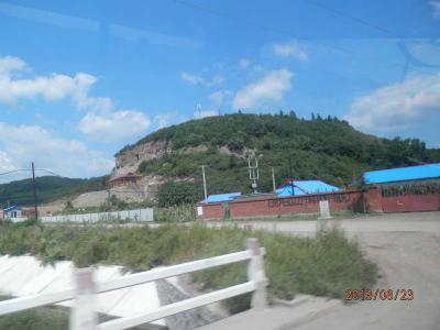 23金曜3日目7午前北京図門長春 車窓から朝鮮族の村と入り口には慰霊碑