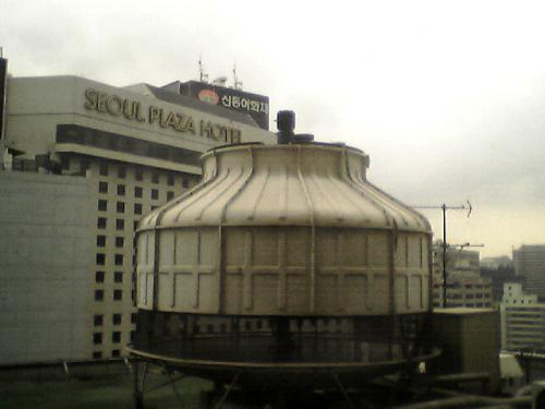 プレジデントホテルの窓から<br />泊まった宿はソウル市役所前のプレジデントホテル。<br />安い部屋を所望したら見晴らしが....<br />それでも税抜き一泊シングルW100,200-<br />ソウルは宿賃が高い!