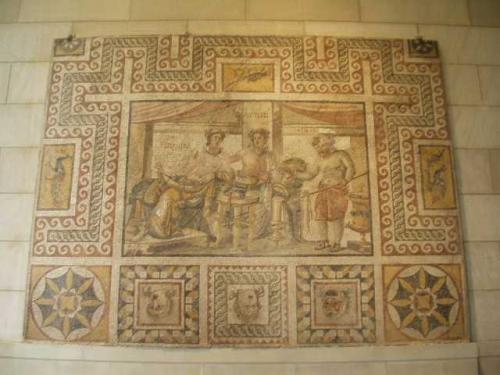アグロスとオポーラ<br />アンティオーク、ダフネ、「プシュケーの小船の家」(3世紀)<br />天然石モザイク<br /><br />古代ローマ人は、長いすにもたれ、食べたり飲んだりしながら何時間も談話に興じた。このモザイクの中の、宴を楽しむ者たちは、アンティオークの豊かな暮らしぶりを象徴する3つの物を表している。がっちりした男性はアグロス(畑)で、美しいオポーラ(果物)と一緒に長いすに座っている。太鼓腹の年老いた召使、オイノス(ワイン)は、水とワインを混ぜる器から2人に飲み物を給仕している。<br /><br />この図像は、アンティオークの裕福な生活を垣間見せてくれる。宴客は、上等な布地に身を包み、ツタのリースと花輪と冠で髪を飾っている。彫刻が施されたテーブルの上には、豪華なカップが置かれ、天幕が贅沢な背景を添えている。<br /><br />モザイクの下部を飾る3つの演劇用マスクは、宴が生きた娯楽であることを暗喩している。右は、サテュロスのマスクで、はげ頭に眉毛をしかめ、口を異様なほど大きく開けている。左の2つの悲劇のマスクは、ぼさぼさの髪にぽかんと口を開け、悲嘆にくれている。このマスクは、部屋に入って来る客に向かって描かれている。<br />