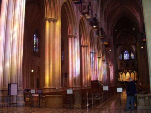 主祭壇に向かって<br />ステンドグラスの色とりどりの光が、列柱に映し出される