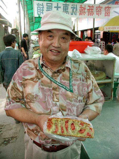 コレは何??<br />大きな丸いケーキのようなモノが売られていまして、地元の人は「很好吃(めっちゃ旨い)」と言うので買いました。<br />持っている人は仕事パートナーの画家爺ぃさんです。