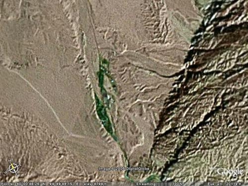 莫高窟上空。<br />北緯:40°00′46.26″<br />東経:94°49′48.15″<br />海抜:1,600m<br /><br />中央の縦割れ緑地が「莫高窟」。その右手にある建造物は「敦煌石窟文物保護研究陳列中心」や駐車場の一角。<br />中央やや上寄りに見える四角く黒い部分は、敦煌研究院。<br />右は祁連山、左は鳴沙山。<br />
