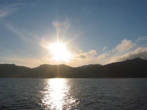 礼文島もだんだん近付いてきました。夕日に浮かぶ島のシルエットです。<br />(9/9)