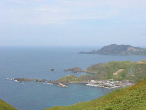 お見送りの後は、人口6人の幻の集落「召国」を訪問する、YH主催のツアーに参加しました。<br />バスで島北部の浜中まで送ってもらい、そこから歩きます。<br />丘を登ると、突然視界が開けて海が広がります。<br />右側に見えるのがが西上泊という集落で、非常に美しい眺めの澄海(すかい)岬があります。<br />(9/10)