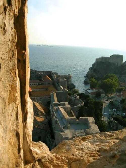 ←◆『ミンチェッタ要塞から見た城壁の道と海♪』<br /><br />ふぅ〜♪やっと一番上まで登って・・おお〜コワ〜(ToT)<br /><br />街を見下ろしましたが、ここは見晴らし台のようになって・・先客が要塞の淵にどっしり座ってしまってた( ̄ε ̄;) <br /><br />そう、とうぜんそれは、例の半裸の男のコ達なんですよ〜<br />彼等はそんな危険な場所に座って、ずぅーーと楽しげに話し続けてたんだけど・・<br /><br />やっと空いた所からは・・これから向うピレ門の上から海に向って伸びる城壁の道が見えました!<br /><br />でも・・「まだまだ遠いな〜」という感じでしたけど(^_^;<br />一通りビデオ撮影して、彼等より先に要塞を降りました(笑)