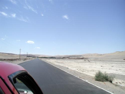 得意(特異?)の箱乗り状態撮影。<br />右半分、砂漠の山肌部分に見える茶色い部分が、砂山の核質部分。石窟の土台になる部分です。<br />中央やや右よりの茶色の台のような部分は、窟の無い壁部分に当たります。<br />緑地部分から右へ繋がった露出部分は、今年初めに「敦煌再発現」としてニュースになった、追加240弱の窟部分です。(2005年現在一般未開放)