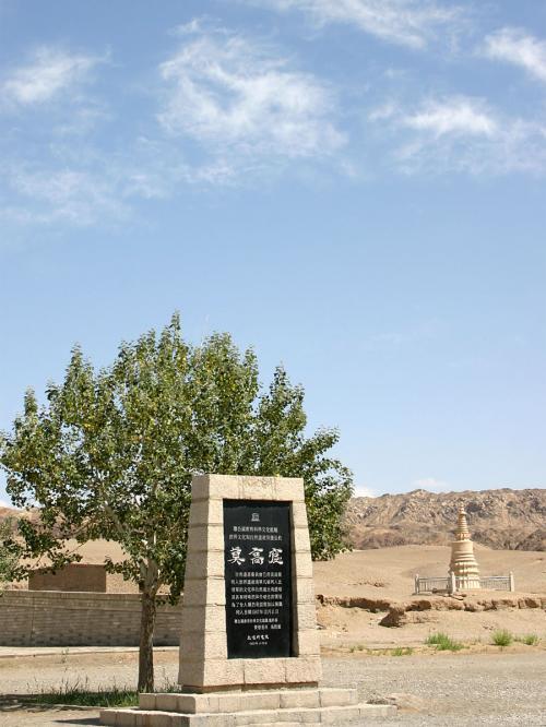 「莫高窟」と標示された世界遺産標識。<br />後にも砂漠上の墓標塔が見えている。