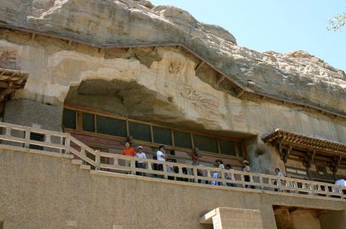 第428窟前にて。<br />石窟の玄関前の壁面にも、豪華な壁画がある。<br />雨風にサラされていく年月・・・この辺りは良く残っている部分でもある。