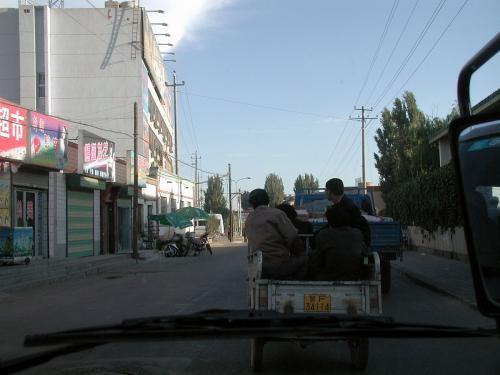 朝の敦煌の町は、トラックやオンボロバスで仕事に向かう人が目立つ。<br />朝日が低いので道が影になっている。<br />北京時間は8時でも、ここの時間では6時前だ。<br />