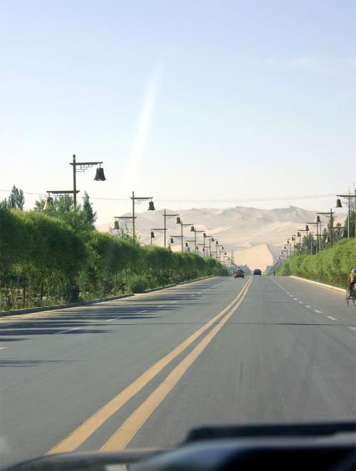 10元で手を打つ運転手は、2人目で見つかりました。<br />早速鳴沙山へ向けて出発〜!<br />でも、5kmしか離れてないので、2分も走ればもうこんな景色です。<br />