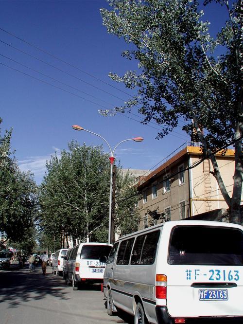 敦煌旅行社のワゴン車がズラリと並んでいた。<br />この時期、観光シーズン真っ盛りだ。<br />(トヨタハイエースベースの「金杯(jinbei)」と言うワゴン)