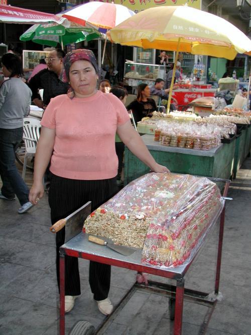 前々から撮しておこうと思っていた、新疆名物のお菓子『核桃仁麻糖』。<br /><br />麻糖売りのこの小母ちゃんとも、暫くもう逢えませんね。<br />彼女は司馬義さんの親戚の方です。