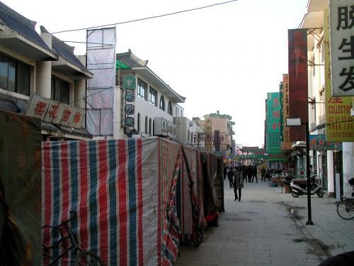 寒い時期のカバブ露店は、こんな感じで簡易的にカバーが掛かっています。<br />もう少し考えて、店をアピールするような柄を選べば良いのに、中国人より考えが簡単な維吾爾人は、「防寒」目的のみ。暖が取れればそれで良いんですね。<br />でも、4月15日からの夜市解禁前なのに、堂々と店を出しているのは凄いです。(^^;<br /><br />カバブは良く焼いて食べればまだ良いでしょうが、ここでの麺類はよした方が良いです。お椀を、洗面器程の大きさの容器に張った、使い回しの水で洗っていますから・・・。<br />帰国時の通関がスムーズに通らなくなりますよ!(^^;<br /><br />この前を通る時、知人の露店で挨拶を交わし、この先の敦煌優名小吃広場(沙州市場内ビアガーデン)で夕食です。