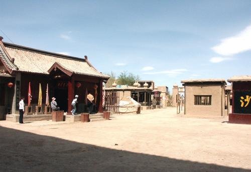 楼閣の門を潜ると、そこにはセットですが町が広がっています。<br />真ん中には「沙州」と書かれた石板があり、コースは左の通りから進むようです。<br /><br />その通り手前の建物に、無料ガイドが待機しています(写真の左際の白服の小姐が立っている後辺り)。
