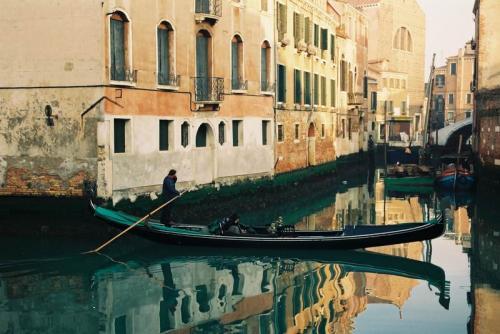 ヴェネツィアはこのときで確か3回目だったと記憶している。何度訪れても魅了される都市がヴェネツィアだ。<br /><br />ヴェネツィア・サンタルチア駅からサンマルコ広場までは、容易に歩ける。細い路地の壁に、方向が示されているからだ。これに沿っていけば問題ない。しかし、私としては、複数回の滞在ゆえ、これまでとは異なるヴェネツィアを垣間見たいと思い、横道へそれた。すると、こんな光景に出会った。普段着なのだろが、絵になる。<br />運河とゴンドラ