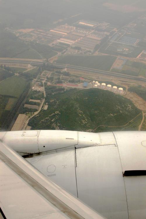 体調と気持ちが何時もとかなり違っていたので、上空からの景色もそこそこに、気付いたら北京上空に到着していた。<br /> <br />上から見ると相変わらず埃っぽい。<br />北京は年中こんな感じらしいが、年を追う毎に酷くなっている気がする。<br />