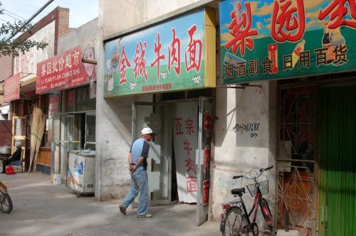 懐かしのあの味、蘭州より旨い蘭州牛肉面の店が!!<br />中心地以外では、看板の色は自由らしい。(ほっ)<br /><br />引っ越ししたその場所は、地元人なら直ぐに判る「医院路」に差し掛かって直ぐの東手(市内から来ると左手)。<br />医院路へは、東大街を敦煌賓館へ向かってきて、ホテルを通り過ごしたら、大きな舗装道路(空港路)に出る。大通りに入たら、直ぐに疎水に架けられた小橋を越える。<br />そこで道が分かれ、左斜め方向に入り込む小さい道がある。これが通称「医院路」で、そちらへ入り込んだら直ぐだ。