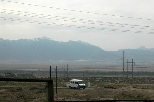 列車は、最初吐魯番へ向かい、そこでスイッチバックする。<br />従って、また暫くは、達坂城の風車などの見覚えのある景色が続いた。<br /><br />画像は天山山脈。(曇りで良く見えず)<br />