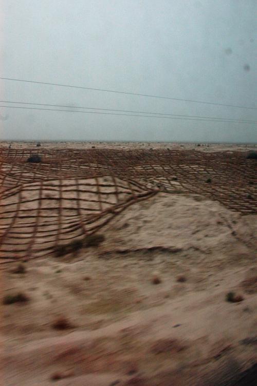 最近、砂漠研究の学者が開発した、地面にワラをネット状に差し込んだ、防砂用設備も沢山見られた。<br />これが見え始めると、駅や町を通過した感じだった。