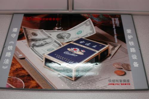 車内にあったタバコ「雪蓮王」の広告。<br />モチーフされている外貨に日本円があったので。。。しかも5千円札だし。