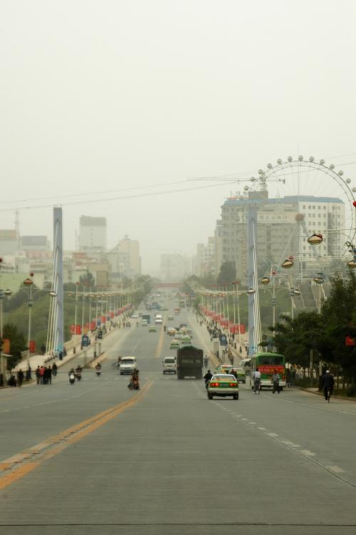 鉄路駅から市内へ向かう幹線道路。<br />観覧車があるけど、遊園地と言うより、単に観覧車乗り場らしい。<br /><br />こんな感じで砂に煙る町喀什に到着した。<br />青空の喀什が多い中、こう言った天気は少ないらしいから、そう言った意味では運が良い・・・とは言いたくない!(`_´#