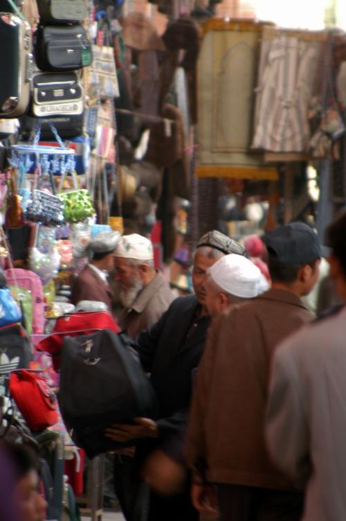 何か、ホント「問屋街」って感じ。<br />この辺りの帽子屋で、クニクニはハンドメイドの花帽子を買う。<br />礼服用などに使う上品なタイプで、被っている人は知識人クラスだという。<br /><br />韓さんが維吾爾語で価格を尋ねると、最初は100元と言いだした。<br />何となく言い出し価格が低く感じられた。<br />すると、、、やはり値切れない。<br />クニクニが、笑いながら手招き交渉。<br /> 店主:「98元」<br /> 国国:「80元」<br /> 店主:「97元」<br /> 国国:「85元」<br />何か、低次元の値切りが続いているけど、シルクの手刺繍帽子は、普通はこんな安い価格では始まらない。地元人と言う事で、最初から即売価格できたようだ。<br /><br />結局、90元で買えたが、クニクニ中々の強者だった。(^^;