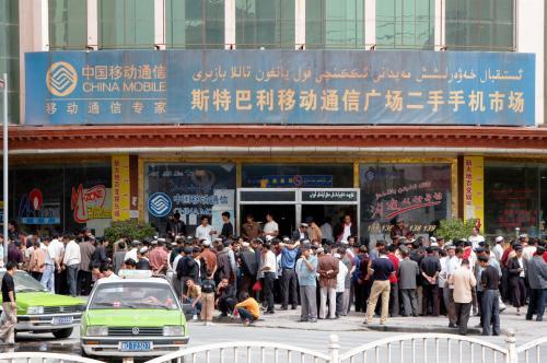 中古携帯電話のお店に群がる維吾爾人客。<br />戈壁灘の辺鄙な所でも、水はなくても「携帯電話」が通じるのだ。<br />前回、霍什拉甫郷(フォスラップ村)でも携帯の送信塔を見かけた。