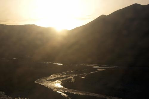 朝日に輝く、天山からの恵みの泉が湧く川。