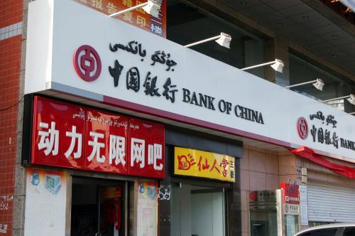 指定を受けた所までタクシーで。<br />目的地はこの近所らしい。<br /><br />降りた所で見た中国銀行。<br />何処にでも有るものなのだが、維吾爾毎の平気が気になったのでパチリ!<br />「動力无限网吧」・・・無限動力のネットバー?