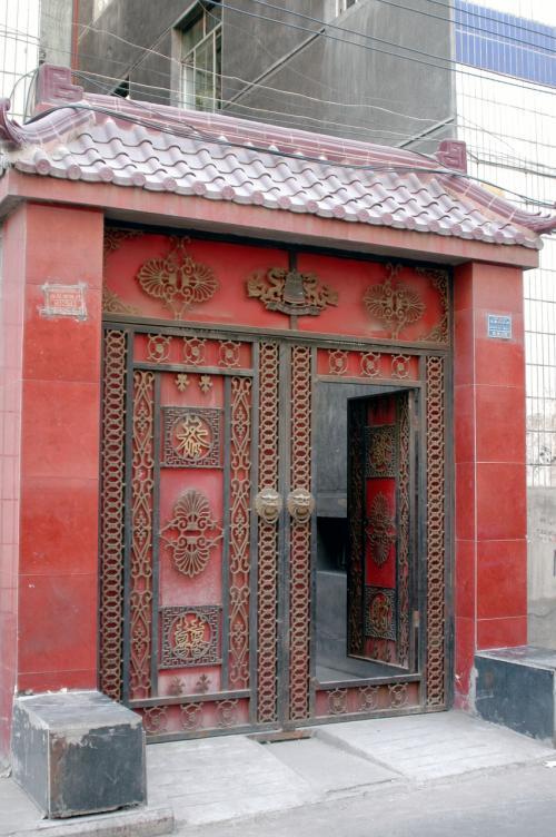 路地には、烏魯木齊の昔ながらの家が有る。<br />この鉄の門が立派で、今の赤色とは違った朱色系ワインカラーだった。<br />