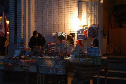 壁に白熱球を掲げ雑貨を売る露天商。