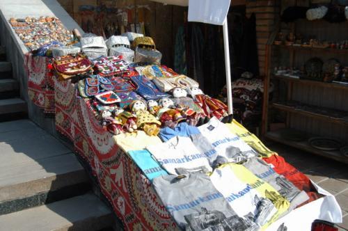 民芸品+Tシャツ。Tシャツが目新しい、以前はなかったからだ。階段を利用して商品を並べている。下に敷いてあるのがスザニ、これも工芸品。