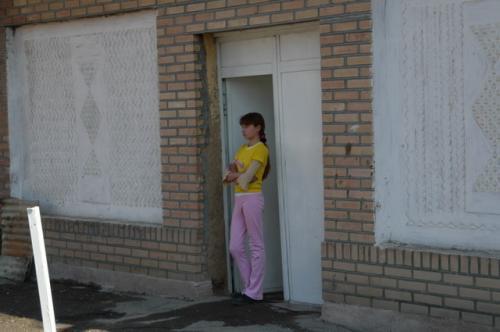 住宅の門から少女が顔をのぞかせた