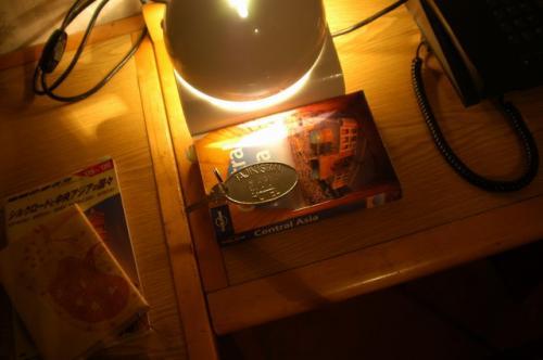 アルミ製のキーホルダーとベッドサイドテーブル、その下は、わが愛読書、Lonely Planet、これがけっこう実が詰まっている。