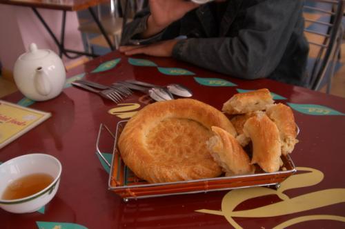 ラグマンを注文し、待っている間にリピョーシカをつまむ。ウズベキスタンでは、最も年下の人がリピョーシカを小さくちぎり、お茶を注ぐのが礼儀。このリピョーシカ、焼きたてて温かかった。