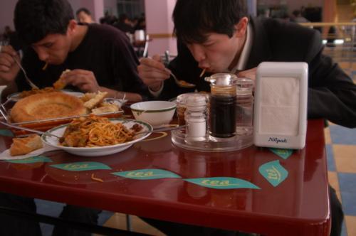美味しい美味しいとフライドラグマンを食べる通訳とドライバー。二人とも20代のウズベキスタン人。