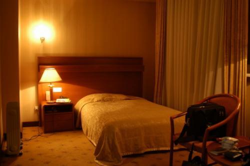 シングルベッド、なかなか快適なベッド。並だろうけど。こうして撮影するとなかなか良い雰囲気だ。部屋の真ん中にテーブルセットが置いてある。
