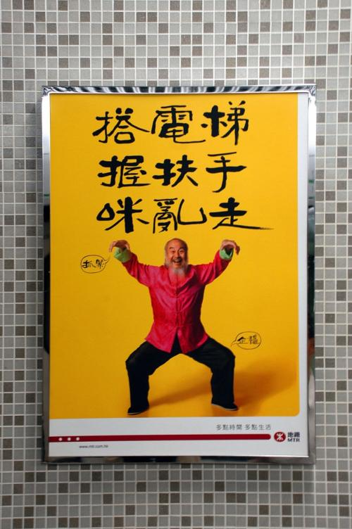 構内のあちこちにある、「エスカレータに乗る時は、しっかりと手摺りを掴んで乗りましょう!」の広告。<br /><br />決して爺ぃが変装しているのではありません。<br />(こんなにスリムじゃないし・・・。(*灬☆)\バキッ!アタタ!)