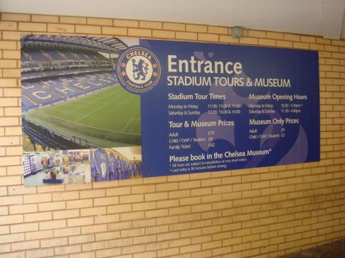 メガストアの隣にあったスタジアムツアーの案内。ツアーの申込みはこの案内板の横のドアから入ったスタジアム内の専用カウンターでした。<br />