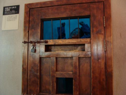 鉄格子の小さな窓しかない鍵のかけられた扉。