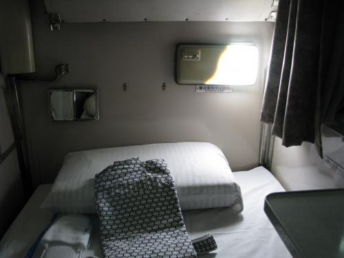 指定されたのは12番下段です。<br />すでに寝台がセットされています。B寝台に比べれば広いですが、寝台料金が高すぎますね。<br />同じ値段で、そこそこ良いホテルに泊まれる値段ですからねぇ〜利用者が減る訳だ。<br /><br />発車前に車掌さんが「寝台券を拝見しまーす」とやってきました。<br />それにしても車内をウロチョロするマニアが多いこと。<br /><br />隣の寝台は親子連れのようで、上段寝台ではしゃいでいる。そうそう子供時ってなんか上段寝台に憧れていたなぁ
