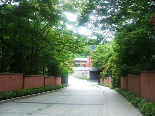 八瀬離宮へのアプローチ(写真)。茶褐色の塀と新緑の木々が古都「京都」らしさを演出している。何となく高級料亭に入っていく雰囲気がする。