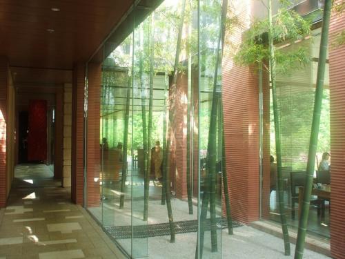 外観は京風料亭であるが、一歩、店内に入ると斬新なデザインに驚かされる。ガラスで仕切られた竹の庭園(写真)越しにレストランのテーブル席が見える。