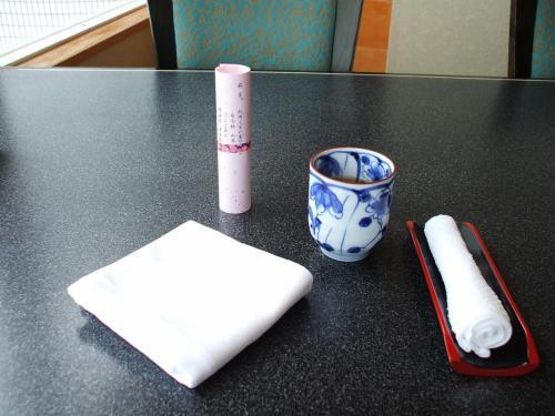 窓側の席に案内され、ゆっくりお茶を飲む。ピンク色した筒状の巻物はお品書き。