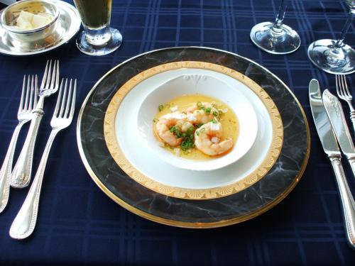 オードブル2:小海老のスパイシーオリーブオイル焼き  前の皿が真白だっただけに、今回の濃紺と金色の混じった皿が引き立つ。小海老はオリーブのほどよい味がして実にうまい。