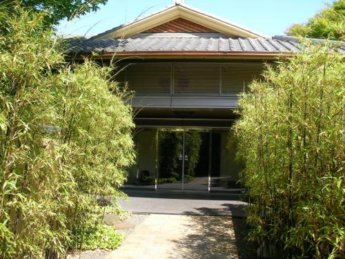 入り口の門を抜けて敷地内へ入り、木々に囲まれた庭を進むとその先にある本館へと続きます。