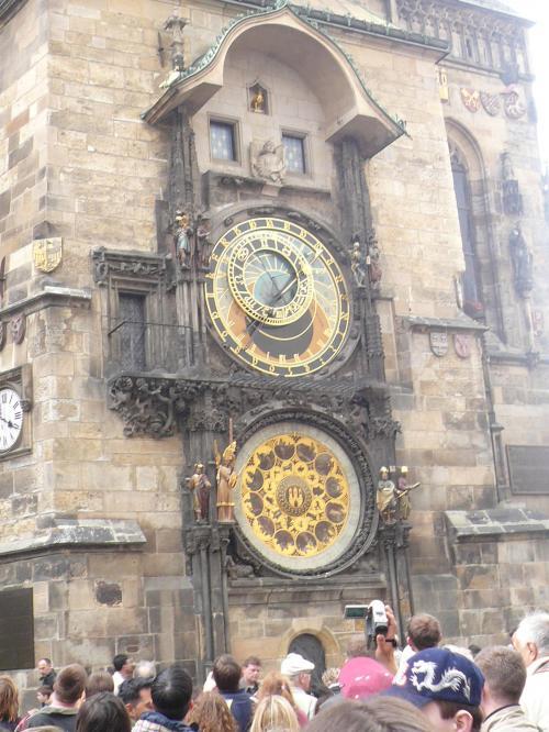 聖ビート教会の天文時計<br /><br /><br />写真は、旧市庁舎にある1410年に造られた仕掛け時計です。上が天文時計で、下が暦板になっていて600年近い歳月を刻み続けている。旧市街中心部にあるこの時計は、プラハを訪れた人なら必ず立ち寄るところです。当時の天文説に基づいた天文の動きと時間を示している。この時計を有名にしたのは毎時窓に現れる仕掛け人形たち。プラネタルームの死神が鐘を鳴らし、塔の上の窓からキリストの12使徒がゆっくりと現れて消えていく。最後は鶏が鳴いて終了する。この瞬間を見ようと毎時、多くの人が集まってくる。<br /><br />