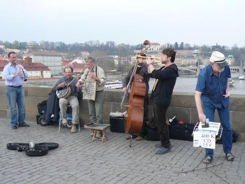 プラハのカレル橋<br /><br />歩行者専用の橋の上では、音楽を奏でる人の周りに人だかりができ、立ち並ぶ絵や民芸品の露店が行き交う人々の足を止める。所狭しと多くの観光客でごった返していた。