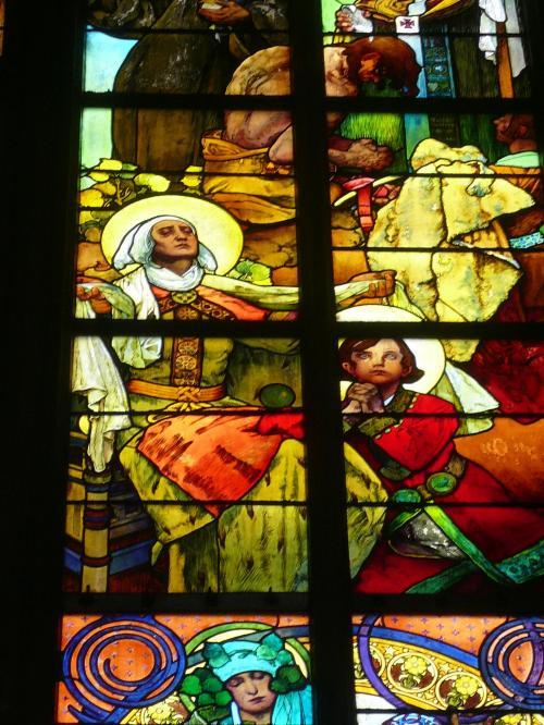聖ヴィート教会のミュシャのステンドグラス <br /><br />聖ヴィート教会のステンドグラスで最も人気の高いのがこの作品で、上写真の中央付近をアップでとらえた物です。写真右下の赤い衣をまとい、手を合わせている少年に注目です。この人は、聖ヴァーツラフと言う10世紀のチェコの王様だそうです。このチェコの守護聖人となった王様の子供の頃が描かれているのだそうです。ムハは、このステンドグラスに、チェコの歴史に登場する重要な人物を、ここに描いているのだそうです。この聖ヴィート大聖堂に来たら、このステンドグラスは、絶対見ておかないと、損ですよ!ムハのステンドグラスは、他のと全然違いました!なんと、チェコにも日本の三種の神器みたいな宝物があるそうです。この聖ヴィート大聖堂にて、それは、それは、厳重に守られています。ミュシャは1939年まで生きていましたから、このステンドグラスもこの教会の中では最も新しいものになります。ミュシャは夢のような女性を描いて日本でも人気のある画家です。カメラのズームで拡大してみると、ミュシャらしさがよく出てきます。<br /><br /><br /><br /><br /><br />